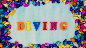 O ` do mergulho do ` da frase, foi afixado no âmbito dos shell coloridos pequenos em um fundo azul foto de stock