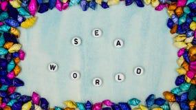 O ` do mundo do mar do ` da frase, foi afixado no âmbito dos shell coloridos pequenos em um fundo azul fotografia de stock