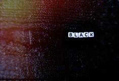 O ` do preto do ` da palavra é feito dos cubos em um fundo de madeira preto Fundo preto, Imagem de Stock Royalty Free