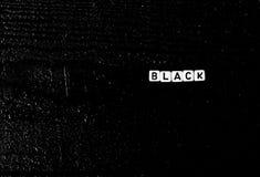 O ` do preto do ` da palavra é feito dos cubos em um fundo de madeira preto Fundo preto, Fotos de Stock Royalty Free