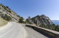 O ` do sinal de tráfego leva em ` próximo do tráfego no fron da passagem na estrada da montanha Imagens de Stock Royalty Free