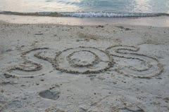 """O """" do """" SOS da palavra escreve na areia na praia Foto de Stock Royalty Free"""