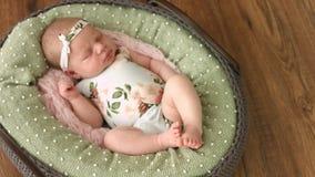O doce menina idosa de duas semanas dorme em uma cesta acolhedor filme