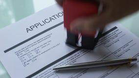 O documento da aplicação rejeitou, mão que carimba o selo no papel oficial, close up filme