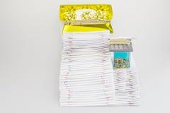 O documento da sobrecarga da pilha tem a curva da fita do ouro e a moeda de ouro Imagem de Stock Royalty Free
