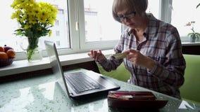 O doente idoso da mulher com artrite reumatoide usando Internet banking na casa filme