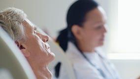 O doente triste envelheceu o homem que escuta seu doutor profissional vídeos de arquivo