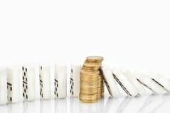O dominó cai em uma pilha de moedas Imagem de Stock