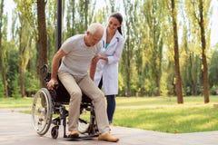 O doutor ajuda o paciente a levantar-se da cadeira de rodas e da caminhada imagens de stock royalty free