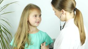 O doutor amigável do pediatra examina uma menina com estetoscópio que verifica os pulmões vídeos de arquivo