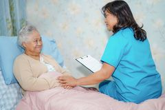 O doutor asi?tico do fisioterapeuta da enfermeira para importar-se, ajudar e apoiar o paciente superior ou idoso da mulher da sen foto de stock royalty free