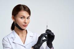 O doutor bonito da jovem mulher na veste médica, na máscara protetora e em luvas pretas médicas guarda a seringa com duas mãos imagens de stock royalty free