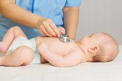 O doutor com estetoscópio escuta bebê Fotografia de Stock Royalty Free