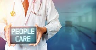 O doutor com o estetoscópio que usa a tabuleta com povos importa-se o texto Conceito da medicina fotografia de stock