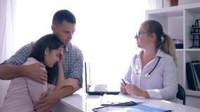 O doutor com más notícias sobre a saúde da mulher, homem abraça sua esposa da virada que senta-se no escritório no hospital vídeos de arquivo
