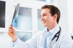 O doutor competente analisa a imagem do raio X Fotografia de Stock Royalty Free