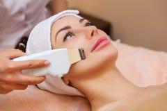 O doutor-cosmetologist faz ao instrumento um procedimento da limpeza do ultrassom da pele facial fotos de stock