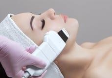 O doutor-cosmetologist faz ao instrumento um procedimento da limpeza do ultrassom da pele facial de um bonito, jovem mulher fotografia de stock