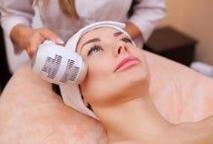 O doutor-cosmetologist faz o procedimento Cryotherapy da pele facial de um bonito, jovem mulher em um salão de beleza imagem de stock royalty free