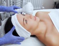 O doutor-cosmetologist faz o procedimento Cryotherapy da pele facial de um bonito, jovem mulher em um salão de beleza fotografia de stock
