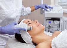 O doutor-cosmetologist faz o procedimento de limpeza do ultrassom da pele facial fotos de stock royalty free