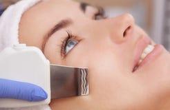 O doutor-cosmetologist faz o procedimento de limpeza do ultrassom da pele facial de um bonito, jovem mulher imagem de stock royalty free