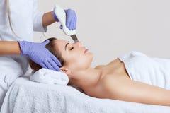 O doutor-cosmetologist faz o procedimento de limpeza do ultrassom da pele facial de um bonito, jovem mulher em um salão de beleza foto de stock