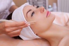 O doutor-cosmetologist faz a terapia do vácuo da cara no mordente de um bonito, jovem mulher em um salão de beleza foto de stock