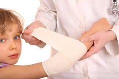 O doutor dá primeiros socorros da criança. Fotos de Stock Royalty Free