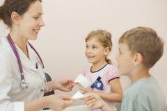 O doutor dá a receita para a menina e o menino Fotos de Stock Royalty Free