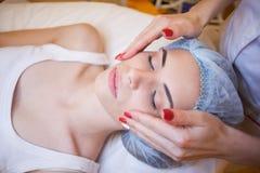 O doutor da cosmetologia faz a massagem do facial dos tratamentos da mulher imagens de stock