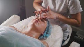 O doutor da mulher executa o procedimento cosmético - mascare a massagem facial no skincare do salão de beleza dos termas imagens de stock