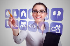 O doutor da mulher que pressiona botões com vários ícones médicos Imagens de Stock
