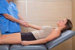 Doutor da terapia de Fascial que puxa o braço paciente da mulher foto de stock
