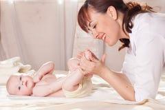 O doutor de bebê do rapaz pequeno que faz as mãos da massagem e os pés e a parte traseira Imagem de Stock Royalty Free