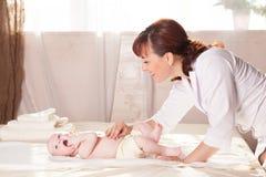 O doutor de bebê do rapaz pequeno que faz as mãos da massagem e os pés e a parte traseira Imagens de Stock