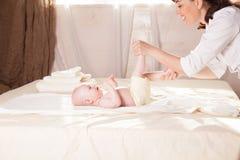 O doutor de bebê do rapaz pequeno que faz as mãos da massagem e os pés e a parte traseira Fotos de Stock Royalty Free