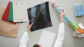 O doutor de Roentgenologist preenche a placa com a descrição da imagem do raio X que senta-se em seu local de trabalho filme