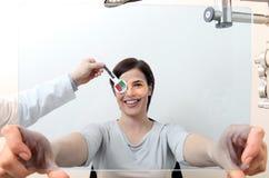 O doutor do ótico do optometrista examina a visão do paciente da mulher mim imagens de stock
