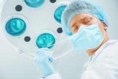 O doutor do cirurgião do homem decola sua máscara protetora imagem de stock royalty free