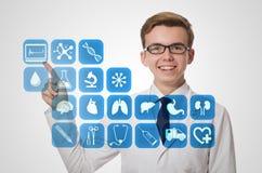 O doutor do homem que pressiona botões com vários ícones médicos Imagens de Stock Royalty Free