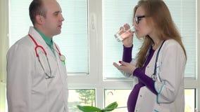 O doutor do médico do colega dá um comprimido e um vidro da água para a mulher gravida vídeos de arquivo