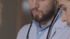 O doutor e dois jovens internam olhando a tabuleta e discutem os resultados da avaliação paciente filme