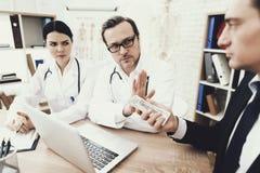 O doutor e a enfermeira honestos recusam tomar o subôrno do paciente no escritório médico foto de stock