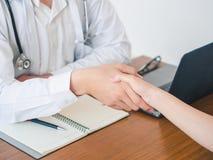 O doutor e o paciente estão agitando a mão no hospital Cuidados médicos e conceito médico fotos de stock