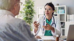 O doutor e o paciente estão discutindo na clínica fotografia de stock