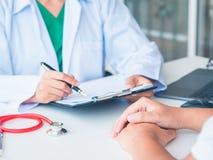 O doutor e o paciente estão falando no hospital Cuidados médicos e imagens de stock royalty free