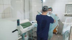 O doutor entra na sala de operações Uma enfermeira ajuda a vestir um vestido do ` s do doutor na sala de operações Preparação par video estoque