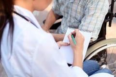 O doutor entrevista o paciente em uma cadeira de rodas imagens de stock