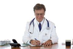 O doutor envelhecido escreve para baixo o sorriso da prescrição Fotos de Stock